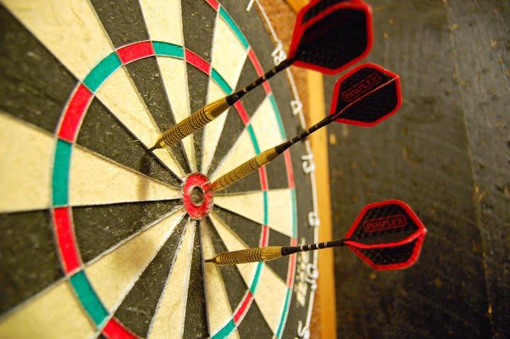Dartbord met darts in de buurt van de bullseye