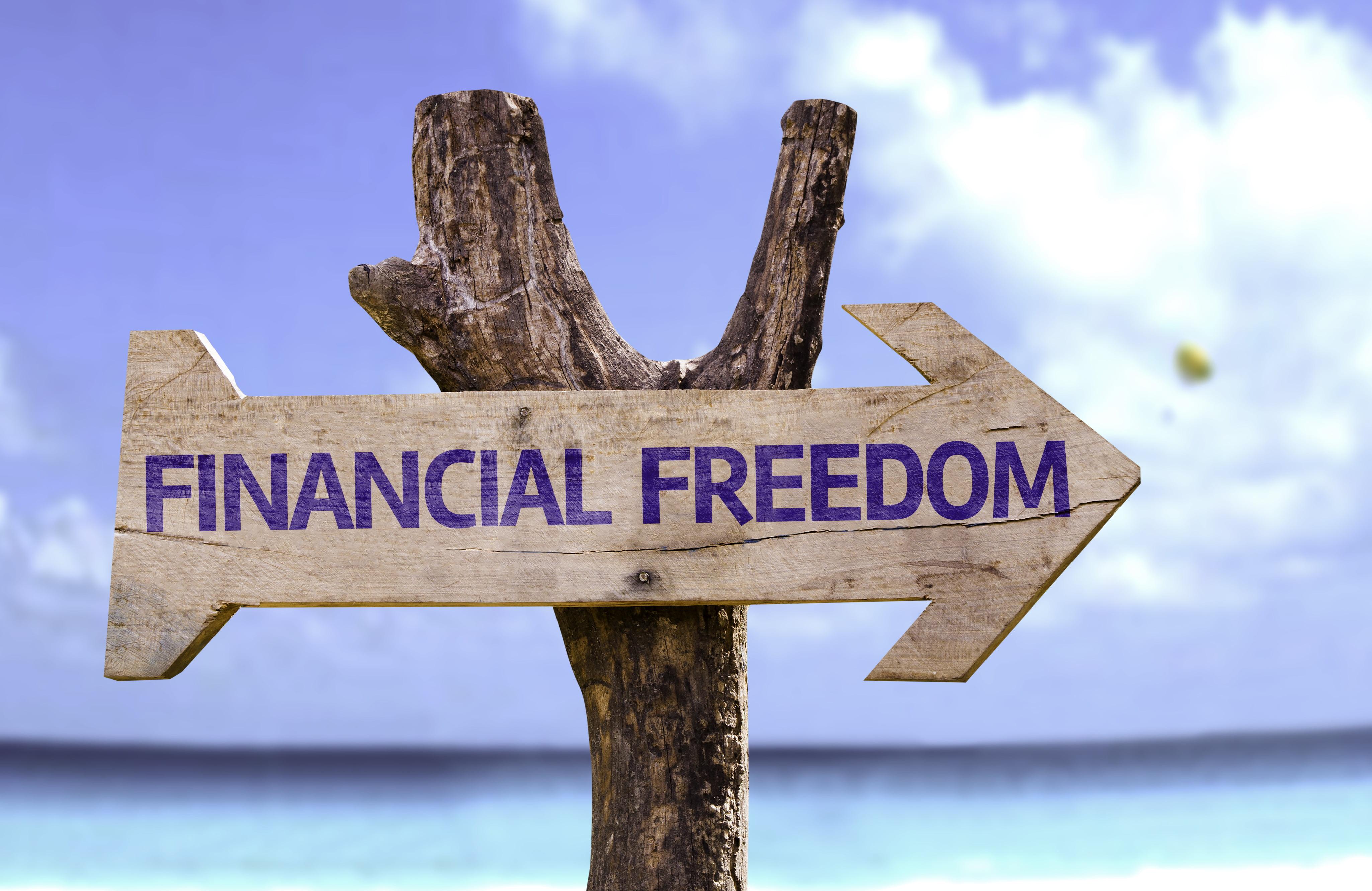 Houten bord met opschrift Financiel Freedom met strand op achtergrond